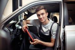 一年轻微笑automechanic在有一个特别设备的一辆汽车坐cheching的汽车的电脑系统 免版税库存图片