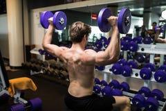 一年轻男性做的重量级的锻炼的背面图与哑铃的 库存照片