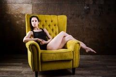 一年轻美丽,有稀薄的图的性感的白种人妇女和长的光秃的腿,赤足摆在斜倚在i的黄色扶手椅子 库存图片