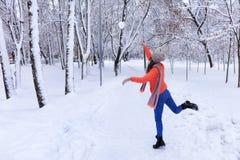 一年轻美女在沿一个胡同的冬天走在一个积雪的美妙的城市公园 免版税图库摄影