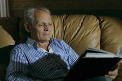 一年长人微笑审查在册页的一张照片 库存照片