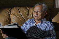 一年长人微笑审查在坐在a的册页的一张照片 免版税库存图片