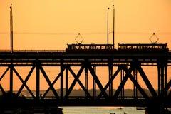 一座两层桥梁和2辆电车的剪影在日落背景 图库摄影