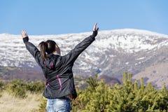 一座冬天山的与开放胳膊-保加利亚年轻旅游妇女 库存图片
