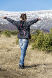 一座冬天山的与开放胳膊-保加利亚年轻旅游妇女 免版税库存照片