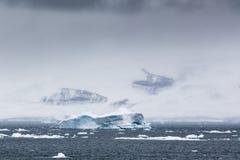一座冰山和山在云彩 免版税库存图片