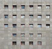 一座办公楼的灰色石现代门面与反射天空的窗口的 免版税库存照片