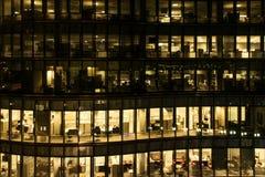 一座办公楼的黄灯窗口在晚上在波士顿夜间在工作 玻璃悬墙办公楼 免版税库存图片