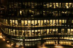 一座办公楼的黄灯窗口在晚上在波士顿夜间在工作 玻璃悬墙办公楼 免版税库存照片