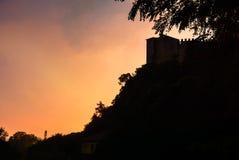 一座城堡的剪影在一座山的在日落 意大利,阿罗纳 库存照片