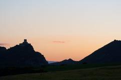 一座城堡的剪影在小山的,在日落 库存照片