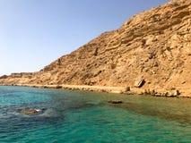 一座大美丽的庄严石含沙山,土墩,小山,小山在反对蓝天和盐绿色天蓝色w的沙漠 库存图片