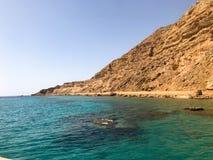 一座大美丽的庄严石含沙山,土墩,小山,小山在反对蓝天和盐绿色天蓝色w的沙漠 免版税库存图片