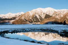 一座山的反射在日落的小池塘 库存照片