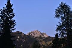 一座山的峰顶在日落的红灯的 图库摄影