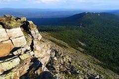 从一座山的峰顶的看法在谷的与森林和多云天空 免版税库存照片