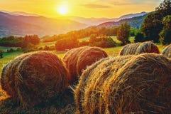 一座山的干草堆在日落 图库摄影