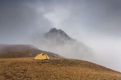 一座山的黄色帐篷和峰顶在雾外面的 免版税库存照片