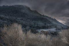 一座山的Snowscape与一个单独房子&树的 图库摄影
