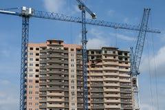 一座新的高层建筑物和三台建筑用起重机 免版税库存照片