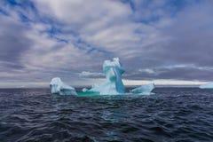 一座显著地形状的冰山在海漂浮反对蓝色和多云天空,南极洲 免版税库存图片