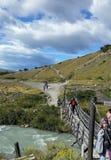 一座暂停的桥梁的远足者在冰川在托里斯del潘恩国家公园,巴塔哥尼亚智利哺养了小河 库存照片