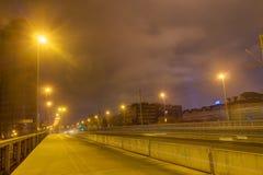 一座桥梁和一条路在与光亮的光的晚上在双方 库存照片
