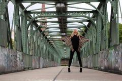 一座桥梁的美丽的白肤金发的妇女有街道画的 库存图片