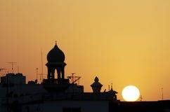 一座清真寺尖塔的剪影在日落期间的 库存照片