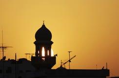 一座清真寺尖塔的精采剪影在日落期间的 免版税库存图片