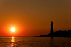 一座灯塔的剪影在落日的背景的 免版税库存图片