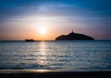 一座灯塔的日落视图在海岛和小船-圣玛尔塔,哥伦比亚的 库存图片