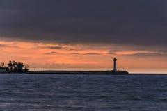 一座灯塔的海景在日出的反对充满活力的橙色天空 免版税库存照片