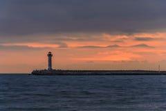 一座灯塔的海景在日出的反对充满活力的橙色天空 库存图片