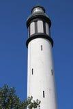一座白色灯塔的上流在无云的蓝天背景的  库存图片