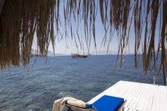 从一座竹平房下面的看法一条美丽的游艇的在l海湾 库存图片