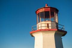 一座红色和白色老灯塔的上面在蓝天的在Gaspesie, 库存图片