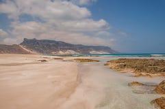 一座美丽的处女海滩、完善的沙子和水和山 库存图片