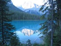 一座美丽的山冠上了与雪,反射在一个原始湖 免版税库存图片