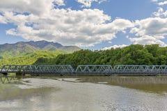 一座老和新的桥梁横渡的大河丝毫山在背景中 免版税库存照片