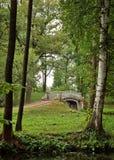 一座老桥梁的看法在树之间的在宫殿公园 库存照片
