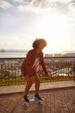 一座被铺的桥梁的踩滑板的女孩 免版税库存照片
