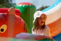 一座跳的城堡的逗人喜爱的小女孩 免版税库存图片