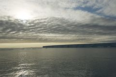 一座非常大冰山的一个美丽的剪影在北极在多云天空下 免版税库存图片