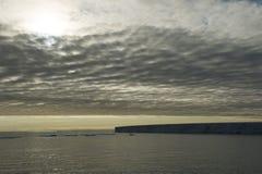 一座非常大冰山的一个美丽的剪影在北极在多云天空下 库存照片