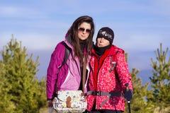 一座高山的两名被装备的远足者妇女 免版税库存照片