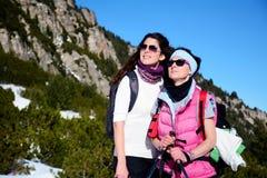 一座高山的两名被装备的远足者妇女 免版税库存图片
