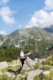 一座高山的旅游妇女在Vihren峰顶背景 免版税库存照片