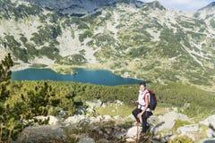 一座高山的远足者妇女在蓝色湖背景 免版税图库摄影
