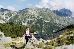 一座高山的远足者妇女在Vihren峰顶背景 库存照片